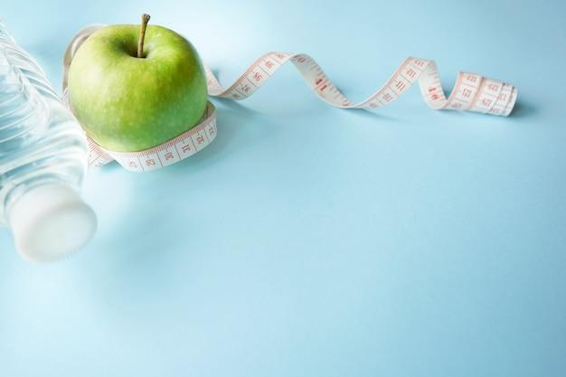 Concepto de un estilo de vida saludable. agua, medidor de glucosa y manzana verde sobre fondo azul.