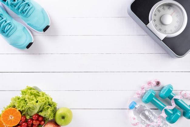 Concepto de estilo de vida saludable, comida y deporte en madera blanca