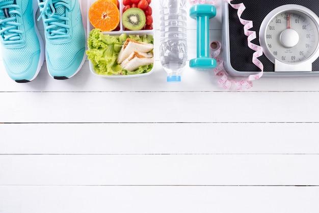 Concepto de estilo de vida saludable, comida y deporte en madera blanca.