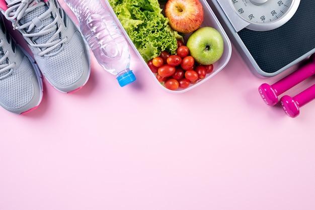 Concepto de estilo de vida saludable, comida y deporte en rosa pastel.