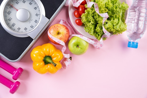 Concepto de estilo de vida saludable, comida y deporte sobre fondo rosa pastel.