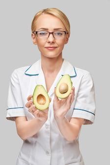 Concepto de estilo de vida saludable médico nutricionista - sosteniendo fruta de aguacate orgánico
