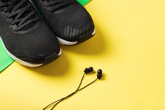 El concepto de un estilo de vida saludable. zapatillas en color amarillo y auriculares para correr