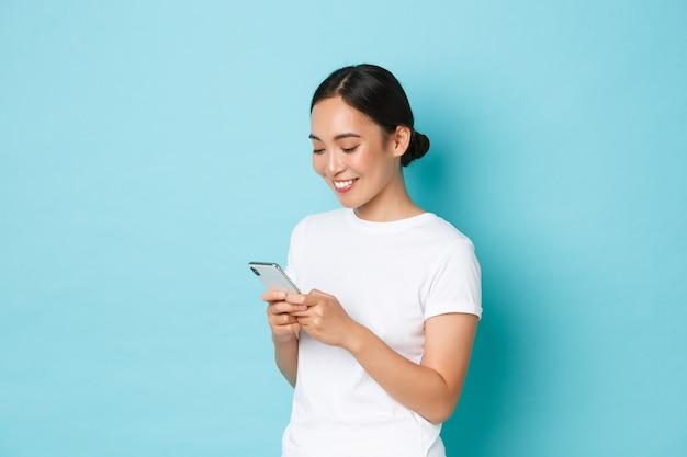 Concepto de estilo de vida, tecnología y comercio electrónico. vista lateral de la atractiva chica asiática que usa el teléfono móvil, envía mensajes de texto, envía mensajes o charla con amigos en línea, mira la pantalla del teléfono inteligente complacida.