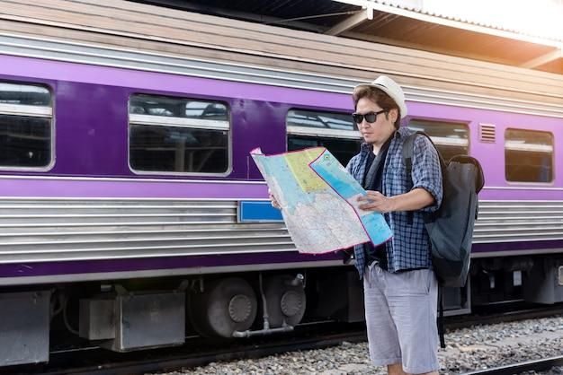 Concepto de estilo de vida vacaciones travel or journey: hombre joven mochilero asiático está viendo el mapa para planificar un viaje en la estación de tren.