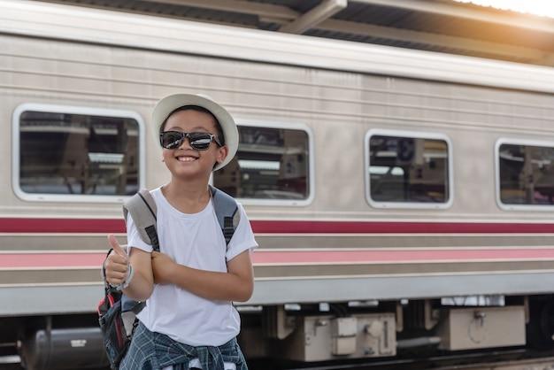 Concepto de estilo de vida vacaciones viajes o viaje: asian kid se cruzó de brazos. y levantando los pulgares en señal de felicidad cuando su familia está de viaje en la estación de tren.