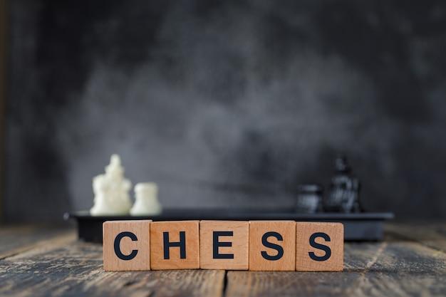 Concepto de estrategia empresarial con figuras en tablero de ajedrez, cubos de madera en niebla y vista lateral de la mesa de madera.