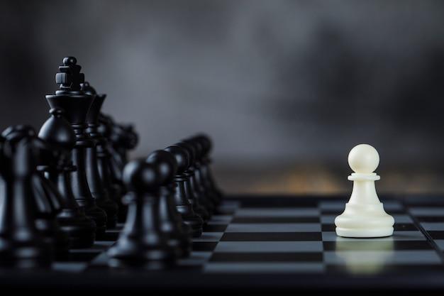 Concepto de estrategia empresarial con figuras en el tablero de ajedrez en niebla y madera vista lateral de la mesa.