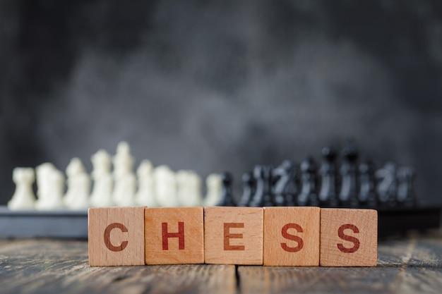 Concepto de estrategia empresarial con tablero de ajedrez y figuras, cubos de madera en niebla y vista lateral de la mesa de madera.