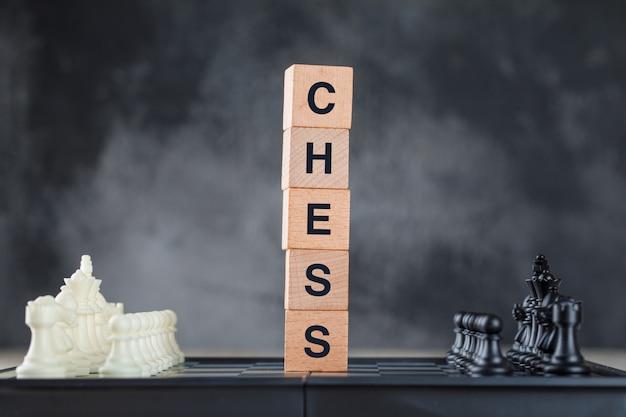 Concepto de estrategia empresarial con tablero de ajedrez y figuras, cubos de madera