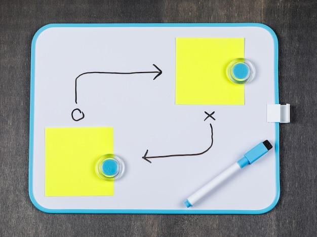 Concepto de estrategia con papel de nota, pizarra, lápiz sobre fondo gris vista superior. imagen horizontal