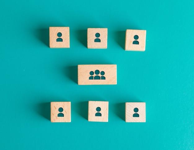 Concepto de estructura de gestión con iconos de personas en bloques de madera en mesa turquesa endecha plana.
