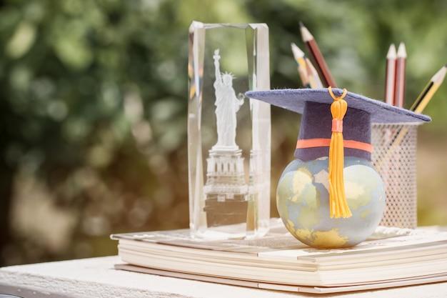Concepto de estudio internacional de aprendizaje en el extranjero en américa: gorra de graduados en el mapa de modelo de globo terráqueo en libro