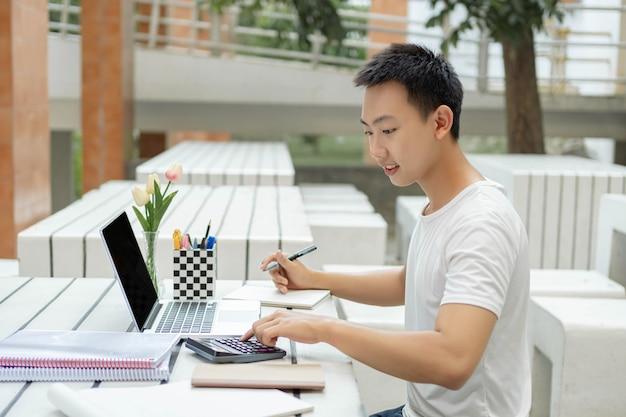 Concepto de estudio en línea un estudiante masculino en camiseta blanca que estudia en línea usando su nueva computadora portátil blanca y la calculadora en la clase de contabilidad.