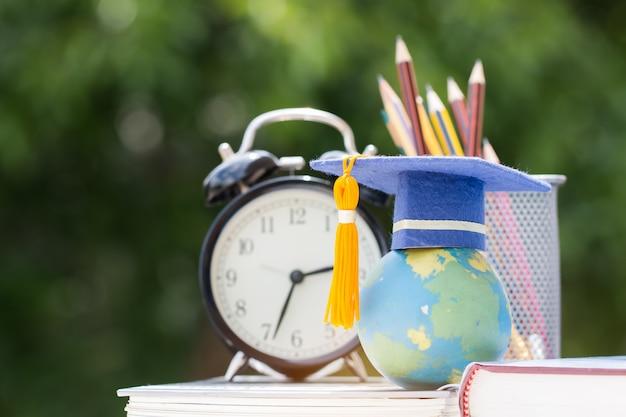 Concepto de estudios en el extranjero para estudios de posgrado o educación: gorro de graduación en un libro de texto