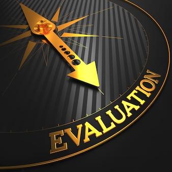 Concepto de evaluación: aguja de la brújula dorada sobre un campo negro apuntando.