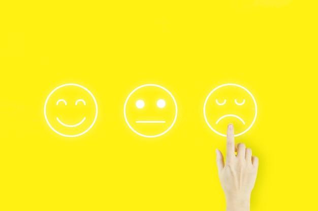 Concepto de evaluación de servicio al cliente. dedo de la mano de la mujer joven apuntando con la emoción de la cara del holograma sobre fondo amarillo. concepto de experiencia del cliente.