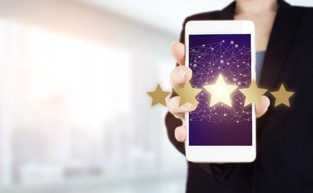 Concepto de evaluación de servicio de producto. asimiento de la mano smartphone blanco con holograma digital cinco estrellas firman sobre fondo borroso claro. mejores excelentes servicios