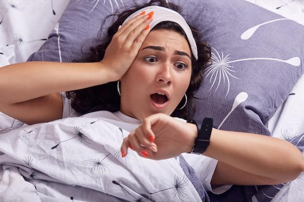 Concepto de exceso de sueño. la joven se perdió el timbre de la alarma, llegó tarde, mira con horror el reloj en la mano, está acostada en la cama, tiene una expresión facial conmocionada, tiene los ojos vendados en la cabeza, mantiene la boca abierta.