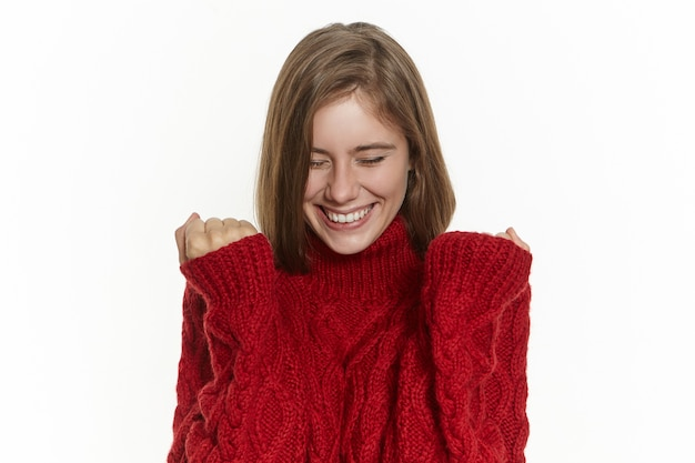 Concepto de éxito, alegría y felicidad. feliz mujer joven emocionada en elegante suéter cálido posando aislado manteniendo los puños apretados y sonriendo ampliamente, regocijándose con las buenas noticias, haciendo realidad su sueño