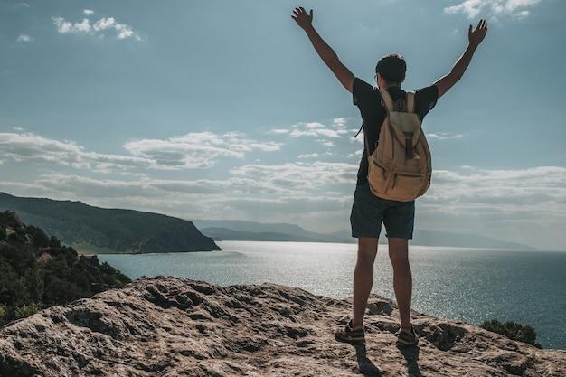 Concepto de éxito. caminante con mochila de pie en la cima de una montaña con las manos levantadas y disfrutando de la vista