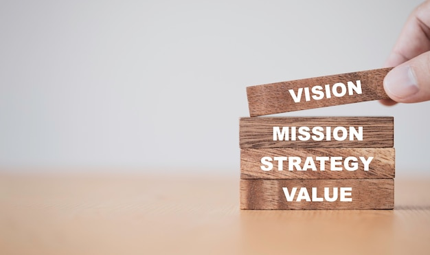 Concepto de éxito clave de la empresa, mano poniendo bloques de cubos de madera que imprimen la estrategia de misión de visión de pantalla y la redacción de valor