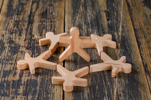 Concepto de éxito empresarial con figuras de madera de personas en la vista de madera de mesa.