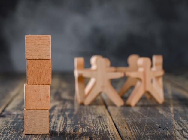 Concepto de éxito empresarial y trabajo en equipo con figuras de madera de personas, vista lateral de cubos.