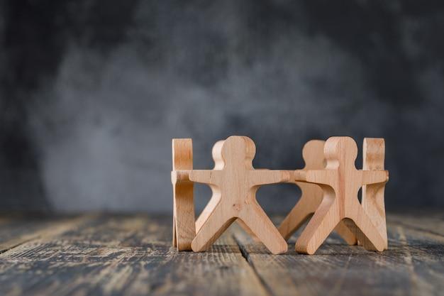 Concepto de éxito empresarial y trabajo en equipo con figuras de madera de vista lateral de personas.