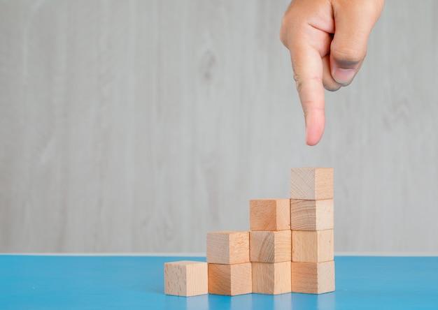 Concepto de éxito empresarial en vista lateral de mesa azul y gris. dedo que muestra la pila de cubos de madera.