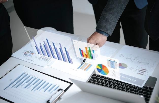 Concepto de éxito de estadísticas de estrategia de finanzas de empresa de gráfico de análisis de plan de reunión de empresarios y planificación para el futuro en la sala de oficina.