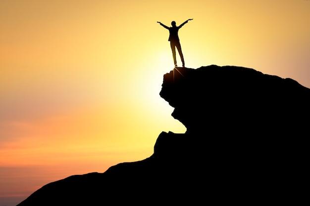 Concepto de éxito y ganador silueta de mujer de negocios feliz parado en la cima de la montaña