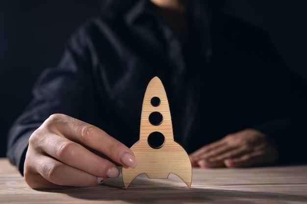 Concepto de éxito, mujeres sosteniendo un cohete de madera