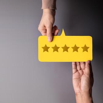 Concepto de experiencia del cliente, cliente feliz dando comentarios de calificación de cinco estrellas sobre la tarjeta a un empresario. vista superior