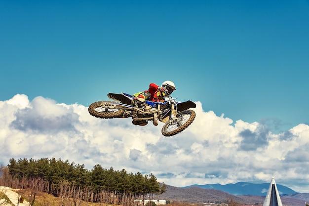 Concepto extremo desafíate a ti mismo salto extremo en una motocicleta sobre un fondo de cielo azul con nubes copie el espacio todo o nada