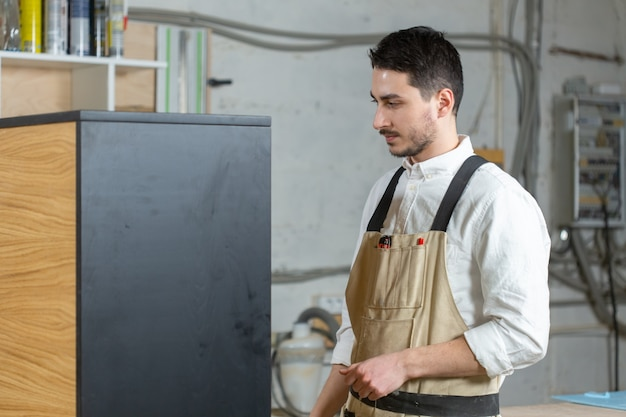 Concepto de fábrica de muebles y pequeñas y medianas empresas: el hombre recopila detalles de muebles