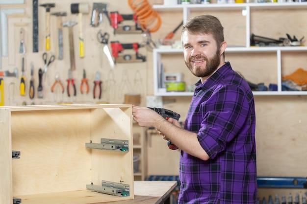 Concepto de fabricación, pequeñas empresas y trabajador - hombre que trabaja en la fábrica de muebles