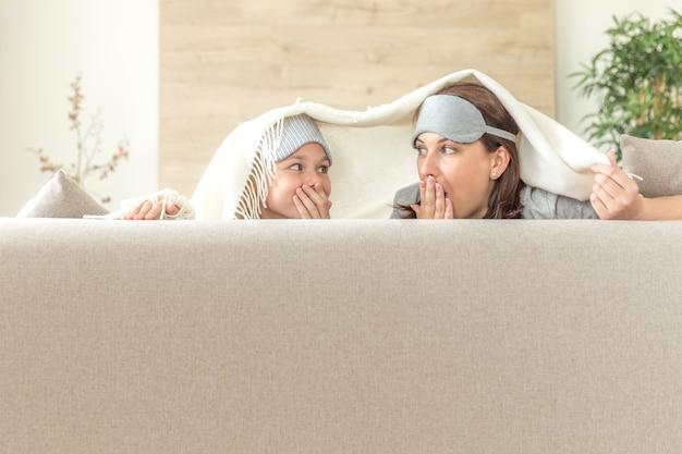 Concepto de familia feliz de madre e hija, vistiendo máscara para dormir y divirtiéndose en el sofá de la sala de estar