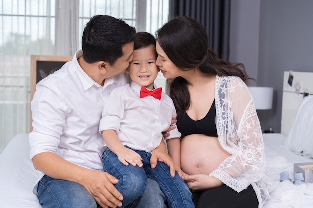 Concepto de familia feliz, madre embarazada y padre que besa al muchacho del niño