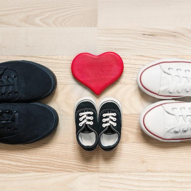 Concepto de familia feliz padre, madre y zapatos de niño pequeño en el piso de madera con corazón rojo. símbolo de crecimiento familiar, diversión, amor, unión, calidez y cuidado. vista superior. espacio para texto