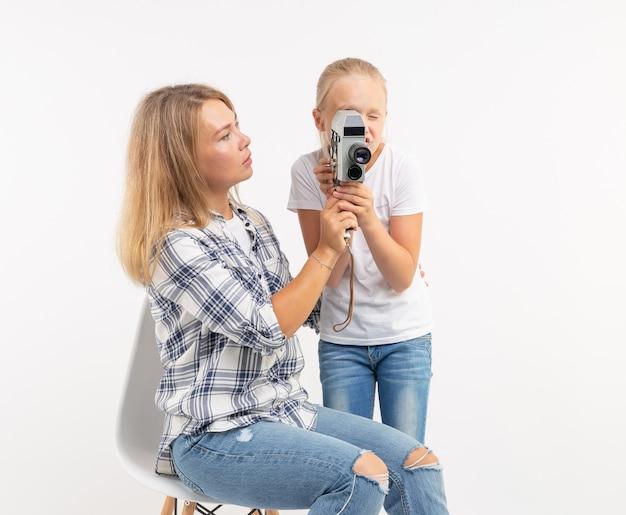 Concepto de familia, fotografía y afición - mujer y su hijo con una cámara antigua.