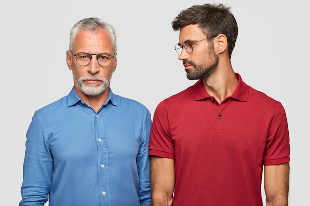 Concepto de familia y generación. hombre maduro de pelo gris con expresiones serias y su hijo adulto que lo mira, pasa el fin de semana en casa, tiene buenas relaciones, aislado sobre una pared blanca