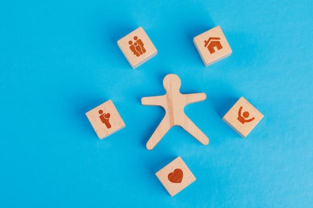 Concepto de familia con iconos en cubos de madera, figura humana en mesa azul plano laical.