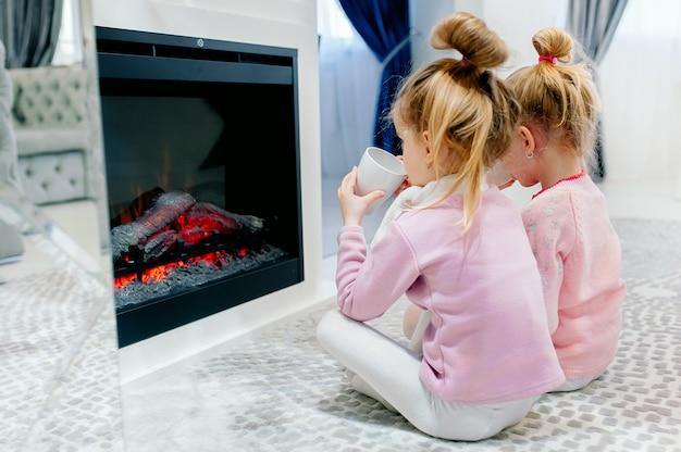Concepto de familia, interior de la casa: son hermanas que juegan juntas. niños felices: hermanas junto a la chimenea