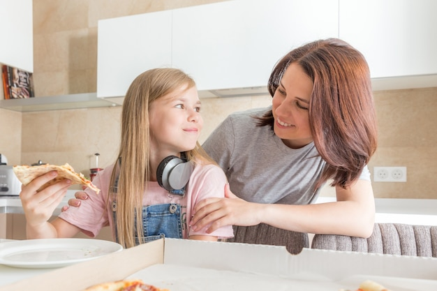 Concepto de familia, madre e hija comiendo una sabrosa pizza