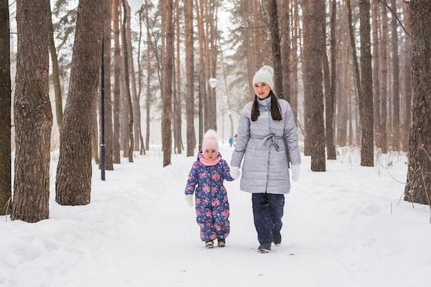 Concepto de familia, maternidad y naturaleza - madre con su hijo caminando en el parque de invierno