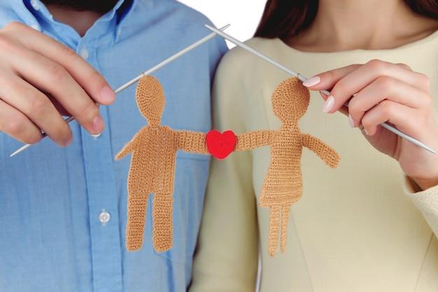 Concepto de familia mujer y hombre con silueta de punto de joven pareja enamorada con forma roja de corazón por agujas de punto