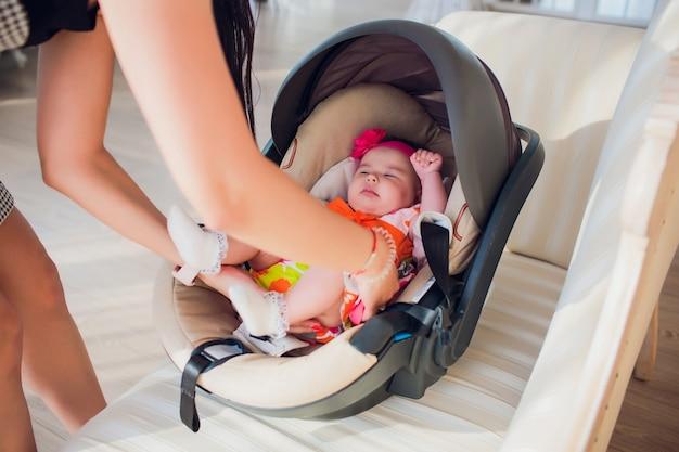 Concepto de familia, transporte, seguridad, viaje en coche y personas: madre feliz arreglando a la niña en el asiento de bebé en casa