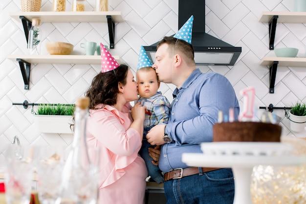 Concepto de familia, vacaciones y personas: madre, padre y pequeño hijo feliz en la fiesta de cumpleaños en casa, los padres besan al bebé