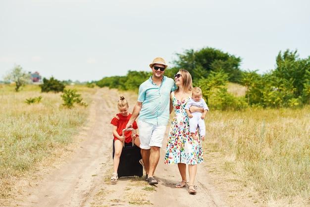 Concepto de familia, vacaciones de verano, adopción y personas: hombre feliz, mujer e hijas en gafas de sol, con maletas divirtiéndose sobre el cielo azul
